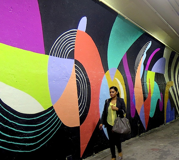 Jessie and katey abstract art mural with passerby DOT Mural Art Beautifies the 191st Street Subway Tunnel and Entrance with: Queen Andrea, Jessie and Katey, RRobots, Cekis and Cope2